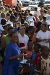 Children line up to receive their gift bag from Santa Claus. Each bag included The Lesson Box by Tregenza A. Roach
