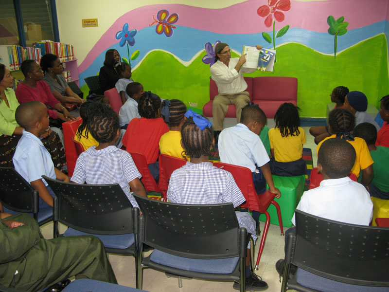"Mario reads to the children from ""A Caribbean Journey"""