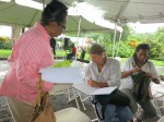 "Mario signs a copy of ""A Caribbean Journey"" to event organizer Dorothy Leevy. Also in the picture is Mara Etienne-Manley, local children's writer, journalist, and founding member of the Dominica Film Association."