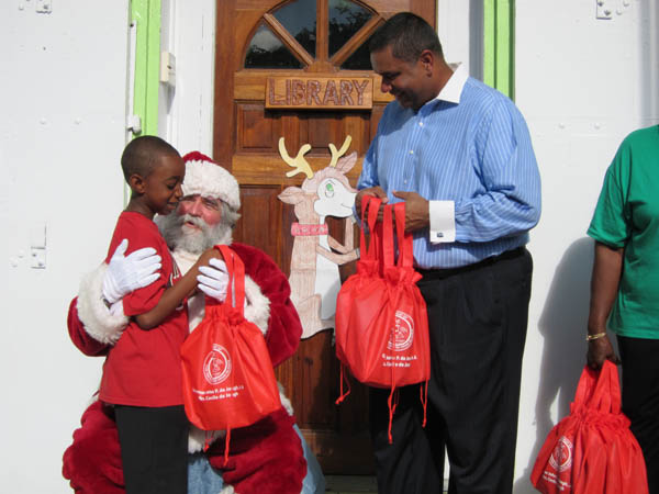 Governor de Jongh helps Santa hand gifts to the children