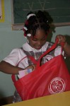 Happy student from St John Christian Academy looks in her gift bag from Santa