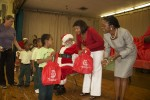 "First Lady of the U.S. Virgin Islands, Cecile de Jongh hands gift bags to the children, while Alscess Lewis-Brown authorofo ""Efa and the Mosquito"" greets and shakes hands with the students. Pearl B. Larsen Elementary School, St Croix."