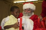 Santa smiles while this young student gets his gift bag. Pearl B. Larsen Elementary School, St Croix.