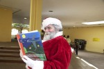 "Santa Claus reads ""A Caribbean Journey from A to Y (Read and Discover What Happened to the Z)"" during a short break."