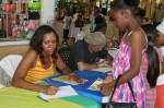 Authors Ashley-Ruth Moolenaar Bernier and Mario Picayo sign books at the Tutu Park Mall in St. Thomas.