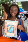 Young reader poses with her new book.